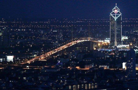 A nighttime view of Bangkok, with the Kasikorn Bank tower and the Rama IX bridge crossing the Chao Phraya river.