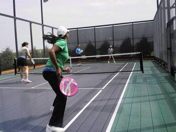 Glenview resident Ami Bilimoria practices during a paddle tennis lesson at the Glenview Prairie Club's new facility.