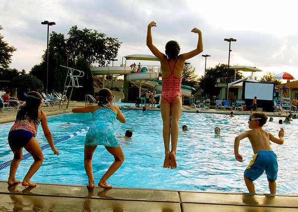 Kids jump into the water at Sunset Pool in Geneva.