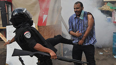 An Egyptian security force member kicks a supporter of ousted President Mohammed Morsi as they clear a sit-in camp set up near Cairo University in Cairo's Giza district, Egypt.