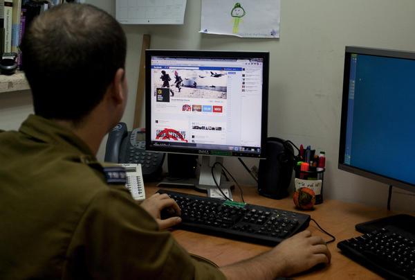 An Israeli soldier looks at the Israel Defense Forces Facebook page in Jerusalem. As many as 550 bilingual students could join a project to post, tweet and blog pro-Israel content in return for scholarships and stipends.