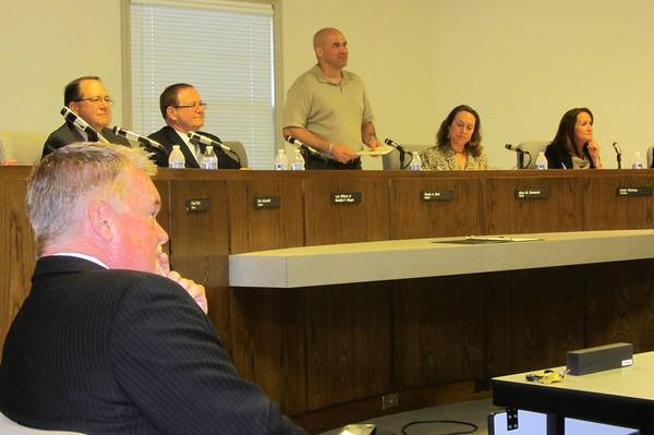 Police Chief Doug Larsson (front) looks on during Monday's board meeting. Mayor Frank Bart (center) said Larsson is out at the end of the month, despite growing support from residents.
