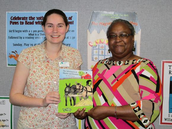 "Patricia Doucet (R) donates copy of ""The Adventures of Blackie and Brownie"" to the Williamsburg Regional Library. Accepting the donation is Youth Services Librarian Hannah Pierce."
