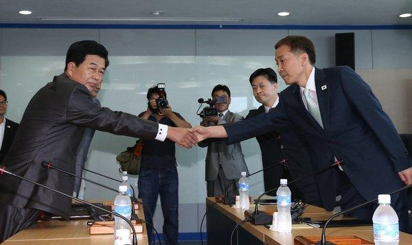 North Korea's chief delegate Pak Chol-su, left, shakes hands with his South Korean counterpart Kim Ki-woong during talks at the Kaesong industrial complex. The two sides reached an agreement on reopening the industrial zone, which was shut down in April amid rising military tensions.