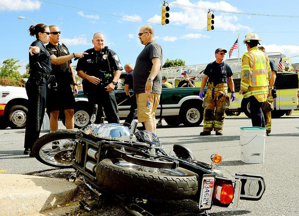 Hagerstown police officers talk with an eyewitness after a Harley-Davidson motorcycle was in an accident with a Chevrolet pickup on Wesel Boulevard near the entrance to Lowe's Wednesday afternoon. Two people on the motorcycle were transported to Meritus Medical Center.
