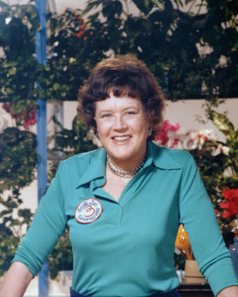 A portrait of the American chef Julia Child (1912 - 2004) shows her standing with a cut of meat in her kitchen.