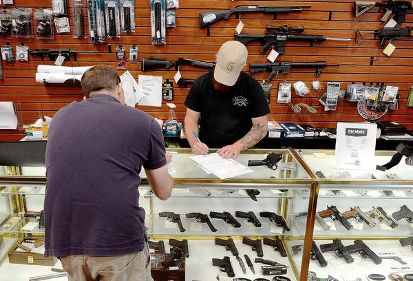 Hendershot's Sporting Goods sales associate Robbie Wood, right, fills out the paperwork for a customer for a regulated firearm transfer at the National Pike store east of Hagerstown.