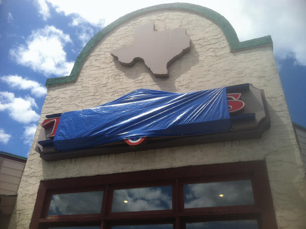A blue tarp covers the sign for the Texas Steakhouse & Saloon on Foxcroft Avenue in Martinsburg, W.Va. The restaurant closed last weekend.