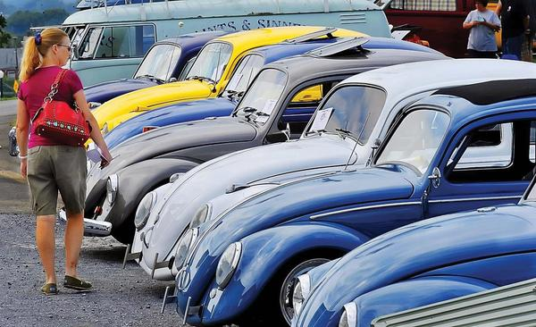 Marlies Blackford of Westminster, Md., looks over a row of Volkswagen Beetles at the 2012 Simple Transport car show at Fairgrounds Park in Hagerstown.