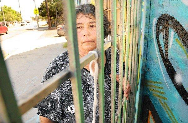 Francisca Pena stands outside the store where her husband was shot to death in 1990. The LAPD recently found DNA evidence linking a suspect to the crime.
