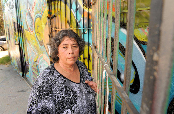 Francisca Pena stands outside the building on San Pedro Street where her husband was shot and killed in 1990. The suspected gunman was arrested Monday after the LAPD found DNA evidence.