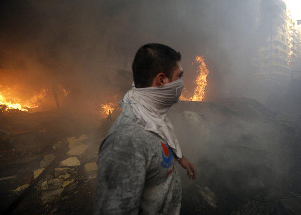 A Hezbollah civil defense worker walks past a burned car following an explosion Thursday in Beirut.