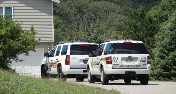 Emmet County Sheriff's Department vehicles sit in the driveway of a Chapel Hill house that was broke into today, Thursday morning. The suspect remains at large.