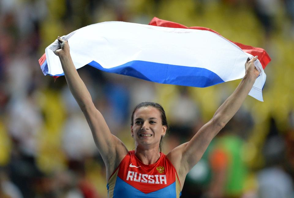 Pole vaulter Yelena Isinbayeva with the Russian flag after winning her third world title Tuesday in Moscow.