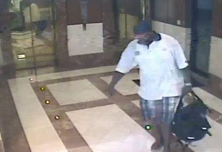 A surveillance image shows a man stealing several laptops in a backpack, police say.