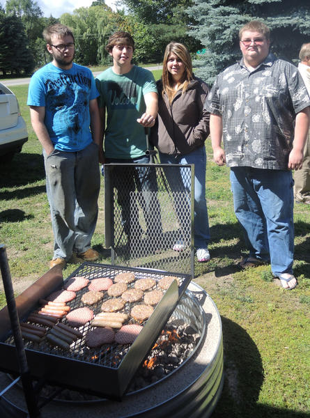 Summer program welding students Devan Honeysette of East Jordan, Aaron Danforth of Boyne City, Sally Swadling of East Jordan and Andrew Beyer of Petoskey wait for the food to cook on the barbecue grill that they made as part of a welding class project. Not pictured are class members Penny Bowling of Charlevoix and Ryan Nesbit of Charlevoix.