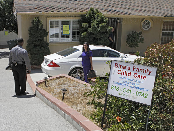 "A woman who showed up to get some things out of the house at 3210 Orange Ave. speaks with Glendale Neighborhood Services and Glendale Police Dept. officials after Bina's Family Child Care was shut down at the home in La Crescenta on Wednesday, August 14, 2013. Officials posted a sign that said ""LIMITED ENTRY. Occupancy Prohibited. No living, sleeping, cooking allowed. Entry limited for purposes of repair only."""
