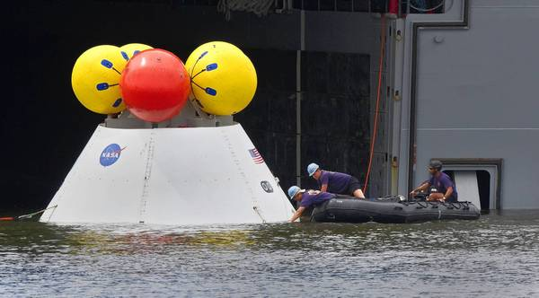 Navy personnel pull in a model of the Orion crew module to the well deck of the USS Arlington during a recovery test at Naval Station Norfolk on Thursday.