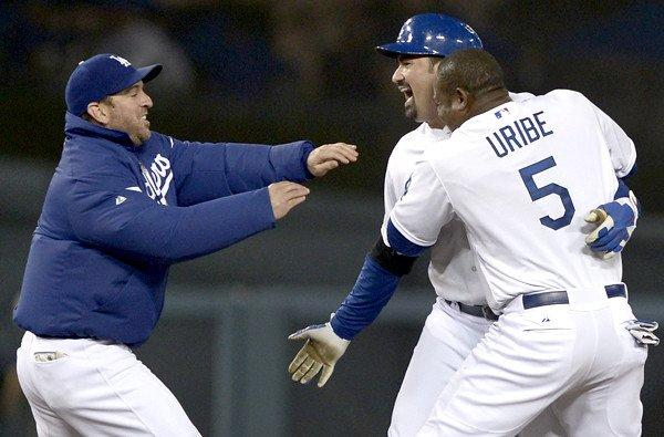 Dodgers first baseman Adrian Gonzalez is swarmed by teammates Juan Uribe and Nick Punto (left) after driving in the winning run against the New York Mets in the 12th inning Wednesday night at Dodger Stadium.