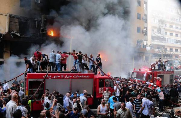 Lebanese civilians and emergency personnel gather at the site of a car bombing in southern Beirut. Some fear the attack is related to the war in neighboring Syria.