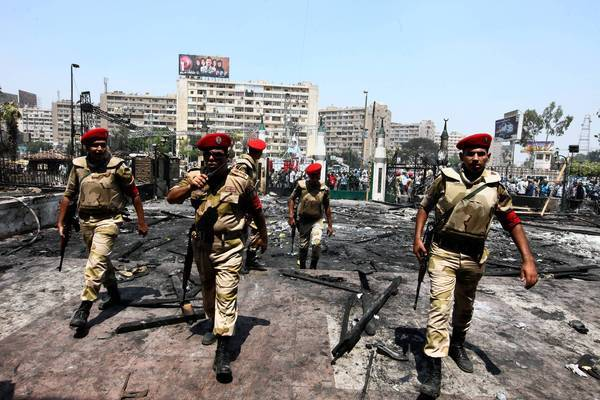 Egyptian troops stand guard at the burned Rabaa al Adawiya mosque in Cairo, where security forces cleared two sit-ins by Islamists demanding the reinstatement of deposed President Mohamed Morsi.