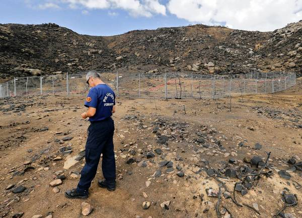 Prescott firefighter Wade Ward visits the site where 19 firefighters died on June 30 fighting the Yarnell Hill fire. Thirteen of those killed were technically part-time workers, and their families are seeking full-time survivor benefits.