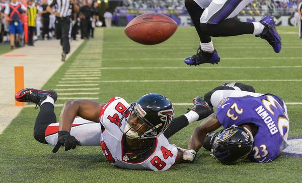 Falcons wide receiver Roddy White can't hang on to a pass in the end zone defended by the Ravens' Chykie Brown during the first half.