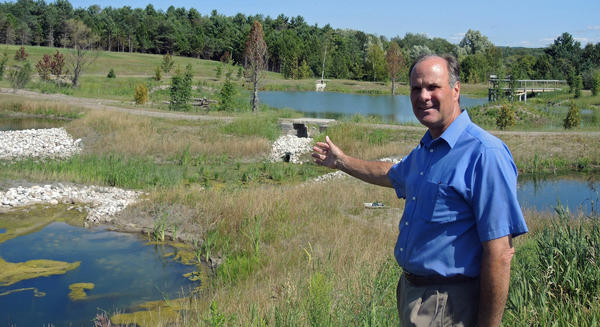 Richard Barber, NCMC's Director of Adjunct Faculty, points out the fore-ponds, viaducts and natural pond created by the watershed project. Barber serves on the university's Natural Areas Committee, which conceived of and oversaw this project.