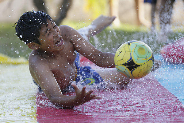 Jose Baltazar, 11, joins friends and relatives in a respite from high temperatures as they frolic on a lawn water slide in Azusa.