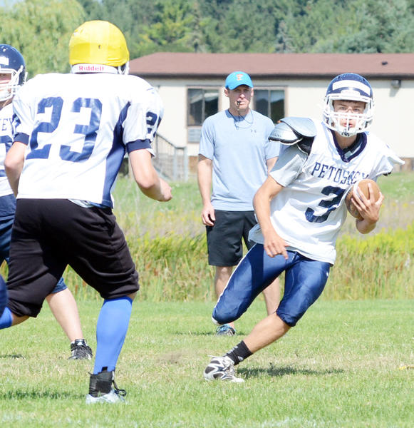 Petoskey sophomore quarterback Evan Whitmore (right) carries the ball during a drill at practice Thursday at the Petoskey High School athletic practice field. Thursday was the first day of padded and full-contact practice for the Northmen and all prep football teams across the state. Petoskey opens the 2013 season on Friday, Aug. 30, at home against Sault Ste. Marie.