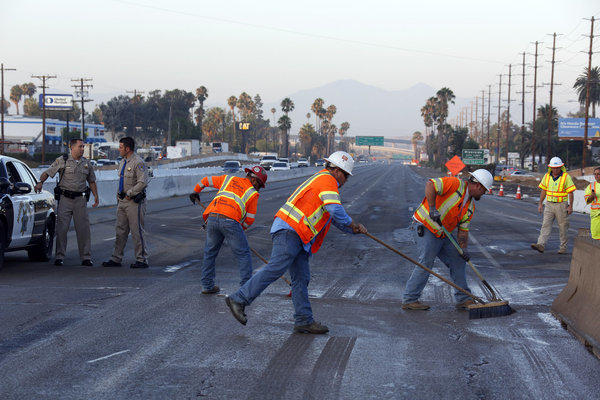 Workers sweep the pavement on a section of the 215 Freeway near Riverside that was closed Friday morning after a construction crew ruptured a gas line.