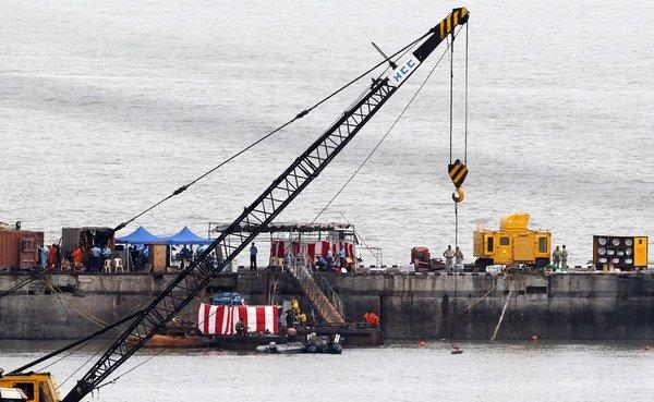 Indian Navy divers stand around the 16-year-old diesel-powered, Russian-made submarine INS Sindhurakshak, covered with a red and white sheet, at the Naval Dockyard in Mumbai on Friday.