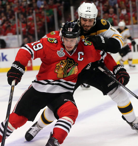 Chicago Blackhawks center Jonathan Toews holds off Boston Bruins left wing Milan Lucic during Game 5 of the Stanley Cup Final.