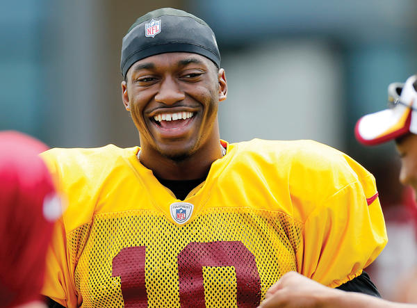 Washington Redskins quarterback Robert Griffin III smiles during practice at the team's NFL football training facility in Richmond, Va., Thursday.