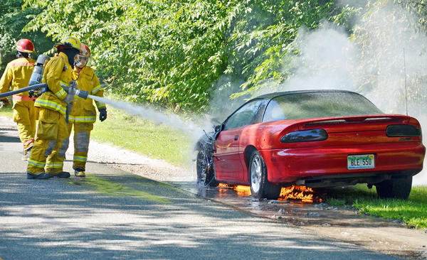 Charlevoix Township firefighters work to extinguish a fire that caused extensive damage to a car parked along Old U.S. 31 North in Hayes Township Friday, Aug. 16.