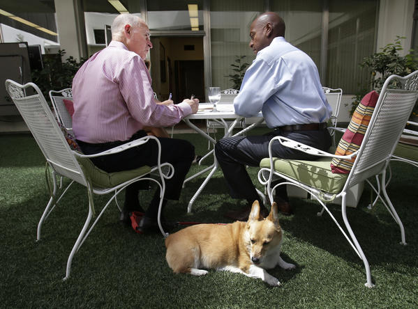 Sutter, the Pembroke Welch Corgi belonging to Gov. Jerry Brown, sits in the sun as Brown, left, discusses a bill awaiting his signature with his Legislative Affairs Secretary Gareth Elliot this week.