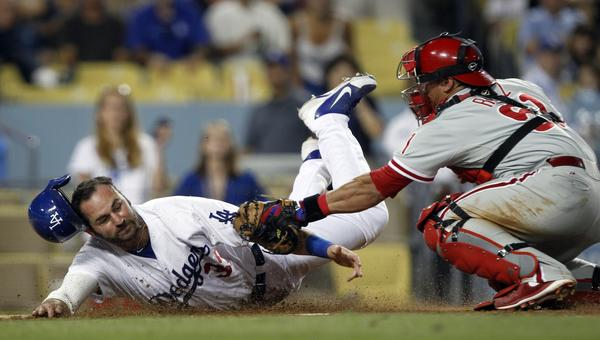 Dodgers outfielder Scott Van Slyke, left, is tagged out by Philadelphia Phillies catcher Carlos Ruiz during a game in June.