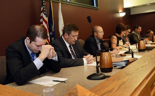 Members of the town board of Greece, N.Y., bow their heads in prayer at the start of a meeting in June. The U.S. Supreme Court will rule whether prayers at government meetings that favor a religion are constitutional.