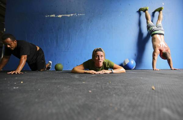"Ramon Aguero, 29, of Apopka, Marla Trautman, 28, and Corey Trautman, 30, husband and wife, both of Altamonte Springs, do ""wall climbs"" during their ""Workout of the Day"" at Altamonte Crossfit in Altamonte Springs, Fla. Friday, August 16, 2013."