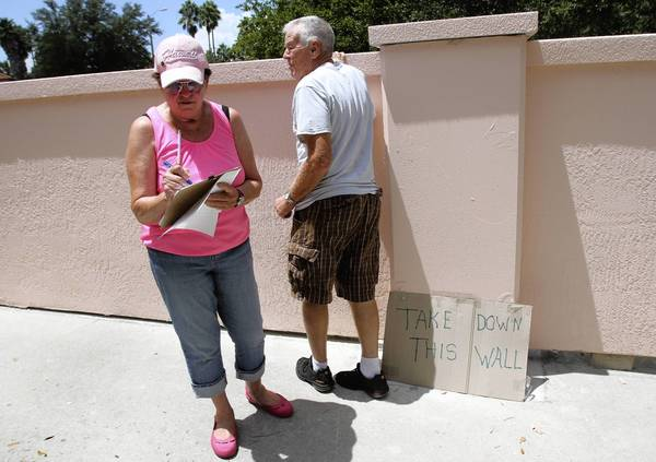 "Josie Chabert, a resident of The Villages , circulates a petition on Wednesday, August 14, 2013. A wall was erected by The Villages developer that has been dubbed the ""Berlin Wall"" because it blocks residents from accessing certain businesses and services with their golf carts. The critics are trying to pressure the developer to ""tear down this wall,"" as Ronald Reagan famously implored of Mikhail Gorbachev, but so far they're getting nowhere. (Tom Benitez/Orlando Sentinel)"