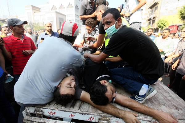 Demonstrators near Ramses Square in Cairo help the wounded after clashing with Egyptian security personnel.