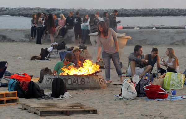 Groups of friends huddle around a fire pit at Big Corona State Beach in Corona Del Mar. The pits have been a gathering point for family, friends and visitors to the beach for years.