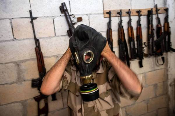 A Syrian rebels tries on a gas mask seized from a Syrian army factory. When the U.S. does deliver its promised weapons to the opposition forces, they are expected to be small arms, not the anti-tank and antiaircraft weaponry the rebels seek.