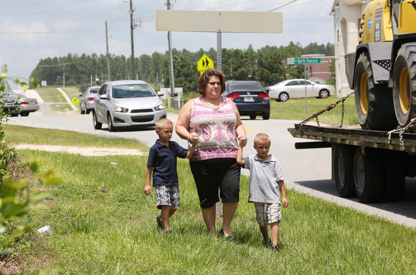 Tara Bush and her sons Kolby and Cody, demonstrate the route they might have to take walking to and from school starting next week.