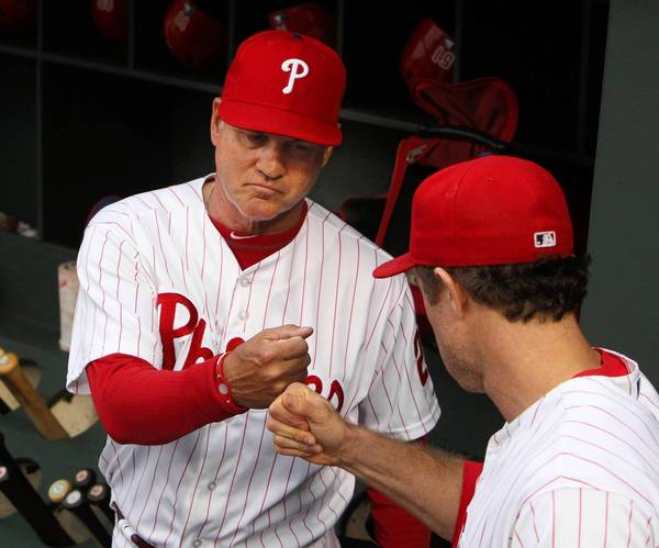 The Philadelphia Phillies' new manager, Ryne Sandberg, is greeted by Chase Utley, right, before the start of action against the Los Angeles Dodgers at Citizens Bank Park in Philadelphia, Pennsylvania, on Friday, August 16, 2013.