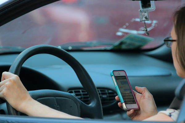 A woman uses a mobile device while driving Friday, Aug. 16, 2013 on West Ohio Street headed into downtown Chicago.