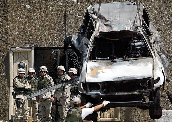 Gen. Ricardo Sanchez, left, and his staff watch as investigators haul away a charred vehicle used in a car bombing at the Jordanian Embassy in Baghdad. As of last summer, the FBI lab had processed about 80,000 IED submissions