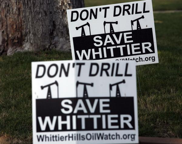 Signs in a Whittier resident's yard show opposition to oil drilling in the city.