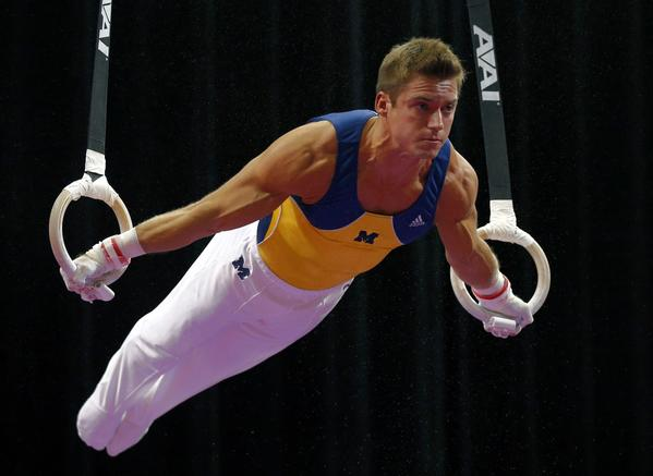 Sam Mikulak performs on the still rings during the men's P&G Gymnastics Championships.