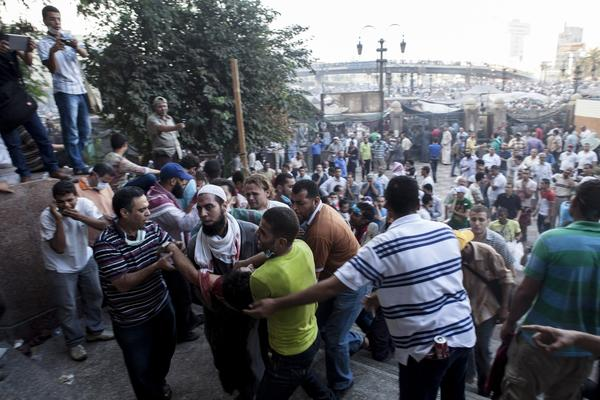 An injured supporter of deposed President Mohamed Morsi is carried into the Fatih Mosque at Ramses Square.
